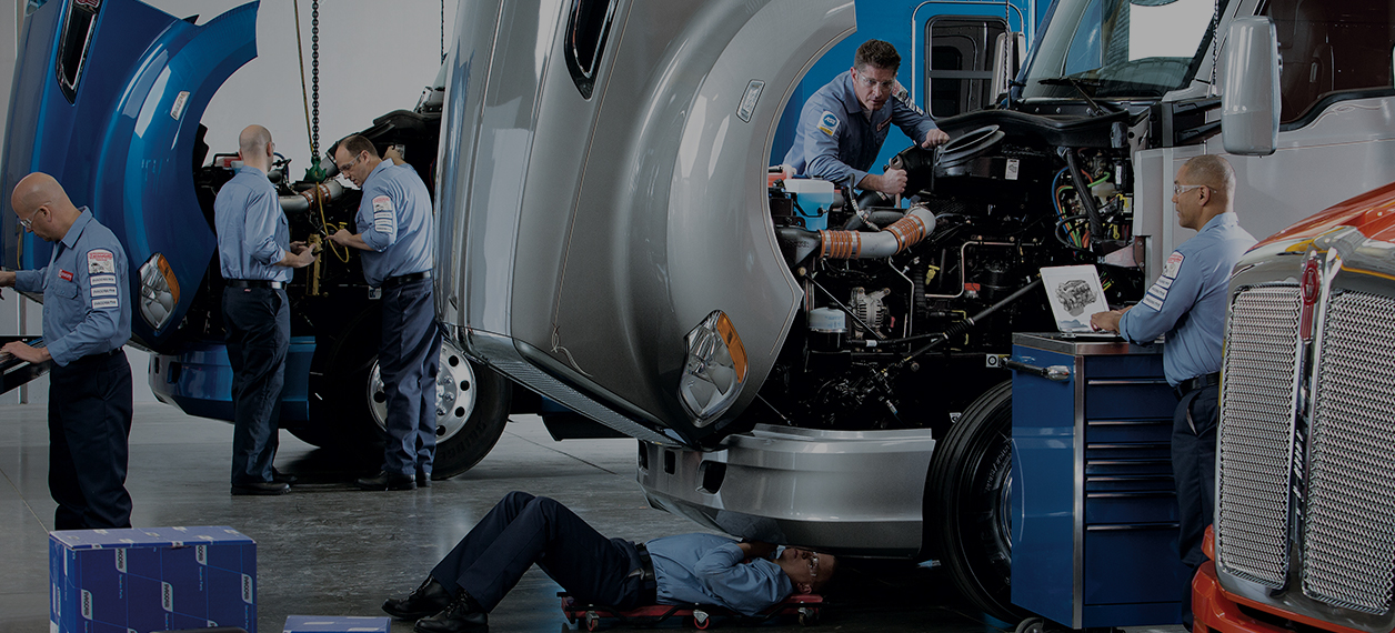 Kenworth mechanics working on trucks in garage