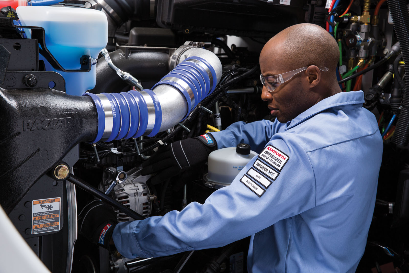 Close up of Kenworth mechanic working on engine