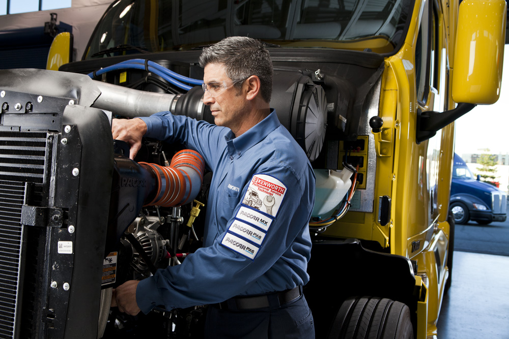 Kenworth mechanic working on truck engine